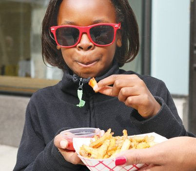 Adilrah Johnson, 8 enjoys fries at Graze on Grace as her mom Shoshana Johnson holds them for her.