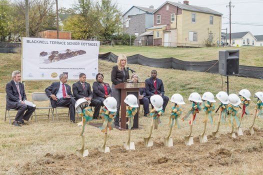 "City Councilwoman Reva M. Trammell speaks glowingly about the 18 senior cottages planned for this site in the 400 block of East 15th Street in Blackwell. Among the dignitaries waiting to don hard hats and ceremoniously break ground are, from left, Richmond development chief Lee Downey, Congressman Robert C. ""Bobby"" Scott, RRHA Chairman Samuel Young, RRHA CEO Adrienne Goolsby, Richmond HUD office director Carrie Schmidt and building contractor Ray Miles."
