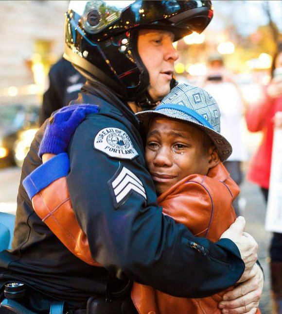 "A black boy holding a ""Free Hugs"" sign stood crying in front of a police barricade at a Ferguson rally ..."
