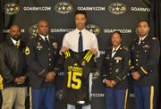 (Left to right) United States Army Representatives Sergeant First Class McConnell; Sergeant First Class McGaskey; and Second Lieutenant Brown at the presentation of a team jersey to Calvert Hall College High School student Lawrence Cager, a standout wide receiver who was selected to play in the 2015 U.S. Army All-American Bowl.