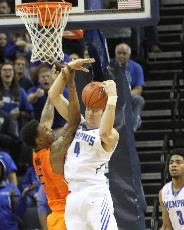 Austin Nichols of the Memphis Tigers grabs a rebound over Le'Bryan Nash of Oklahoma State, recording a double-double (11 points, 13 rebounds). (Photo: Warren Roseborough/ The New TSD)