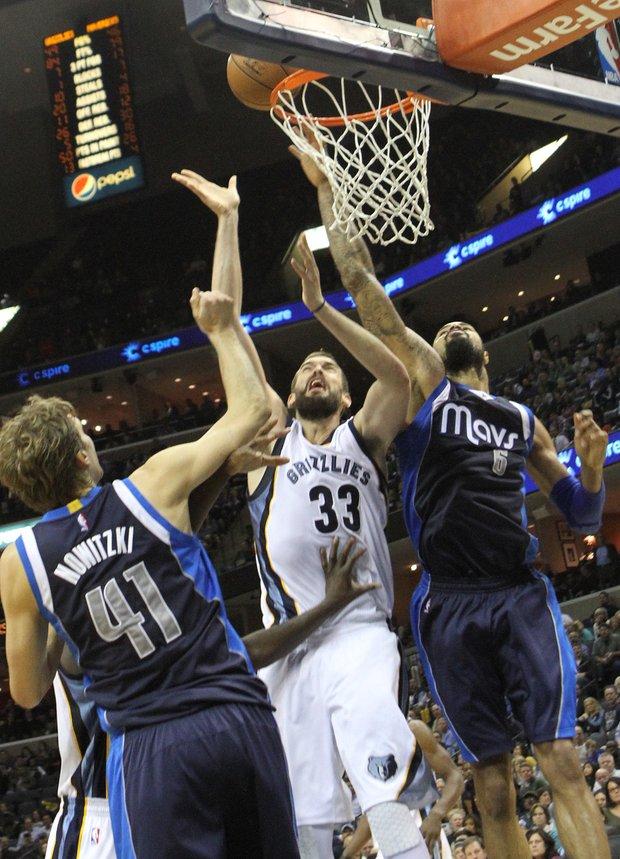 Marc Gasol of the Grizzlies (center) tips in a score over Dallas' Dirk Nowitzki (left) and Tyson Chandler. (Photo: Warren Roseborough)