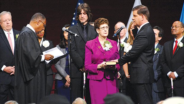 Martin J. Walsh (r) is sworn in by Chief Justice Roderick Ireland, as the first new mayor of Boston in 20 years succeeding former mayor Tom Menino. Looking on are Walsh's family and Boston City Councilors. Holding the Bible is the new mayor's mother.