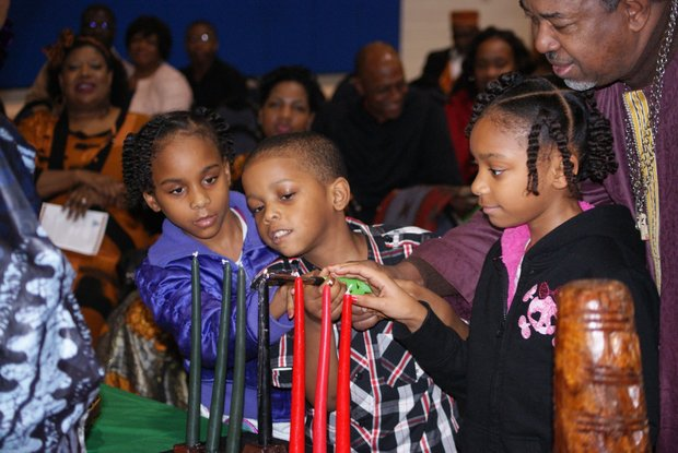The lighting of the Kinara was a team effort involving these children and a little help from Reuben Barnes Jr., aka Diallo Khari, on Day 2 (Kujichagulia - self determination) of Kwanzaa at Brown Missionary Baptist Church in Southaven, Miss. (Photo: Tyrone P. Easley)