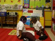 Two young students reading in the Ben Carson Reading Room at John Eager Howard Elementary School in Baltimore.