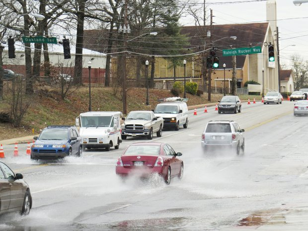 Motorists make their way through water spilling across Candler Road at the intersection of Oakland Terrace and Raleigh Rucker Way.