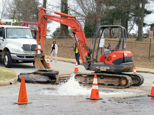 Water pours from a broken water main on Candler Road at the intersection of Oakland Terrace and Raleigh Rucker Way in Decatur.