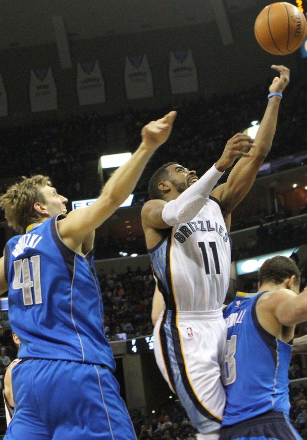 Mike Conley of the Grizzlies scores over Dirk Notwitski of Dallas. (Photo: Warren Roseborough)