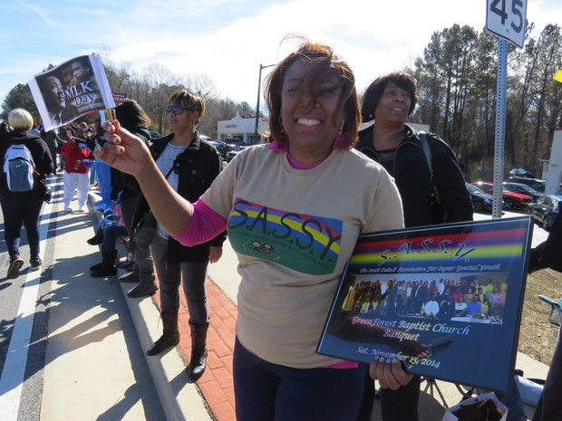 A spectator waves a flag celebrating King Day on Jan. 19 at the DeKalb NAACP's annual parade.