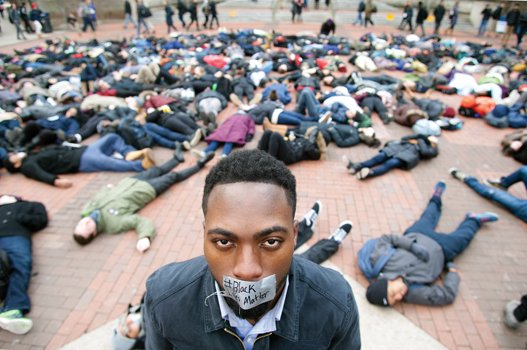 """University of Michigan student William Royster stands with the """"#Black Lives Matter"""" message taped over his mouth as he is surrounded by students at the Ann Arbor, Mich., university staging a recent """"die-in"""" protesting the killing of unarmed black men by white police officers."""