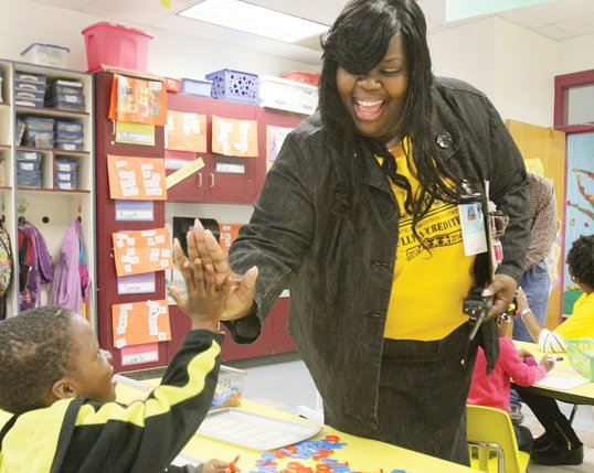 Carver Principal Kiwana Yates gives kindergarten student Jajuan Dickerson a high-five for a job well done.