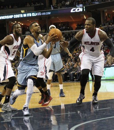 Mike Conley's drive to the basket yields a positive result despite the defense of Paul Millsap of the Atlanta Hawks. (Photo: Warren Roseborough)