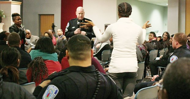 Evandra Catherine asks Richmond Police Officer Jacob DeBoard one of many questions posed Tuesday by community members to department representatives about policing policies during a forum at the Richmond Police Training Academy