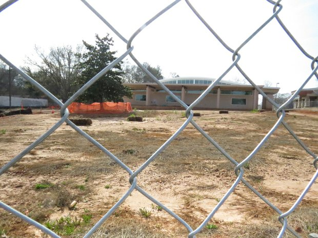 The stalled South DeKalb Senior Center on Candler Road  remains behind a chain-link fence while seniors are being bused across town.