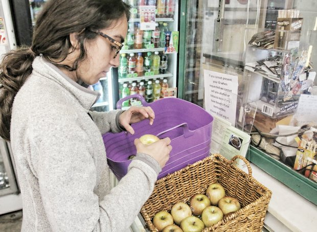 Tricycle Gardens project manager Claire Sadeghzadeh delivers fresh apples and other produce to Song's Market in the East End.