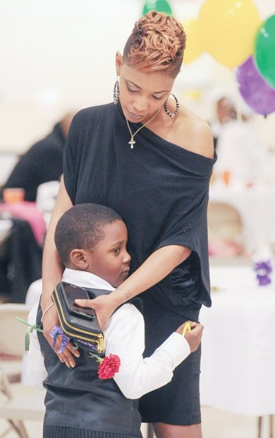 Tanya Wilkins, embraces her nephew, Messiah Gilliam-Cox, as they dance at the Mother/Son and Father/Daughter Red Carpet Dance sponsored by Richmond's J.L. Francis Elementary School PTA.