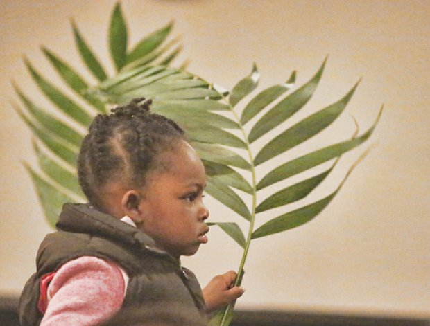 Nyjah Caleb, 2, holds a palm frond at East End Fellowship's Palm Sunday worship service in Church Hill. She and others waved their palms to symbolize the palm branches the crowd scattered in front of Jesus as he rode into Jerusalem a few days before his crucifixion and resurrection that Christians will celebrate this weekend.