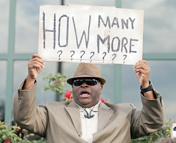 The Rev. Arthur Prioleau holds a sign during Wednesday's demonstration outside the North Charleston, S.C., city hall.