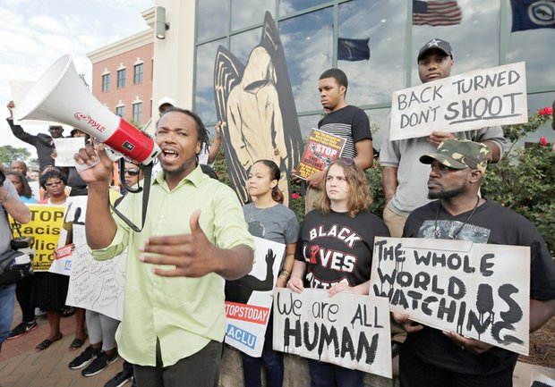 Muhiydin D'Baha leads protesters Wednesday outside of the North Charleston, S.C., city hall in calling for justice in the death of unarmed Walter L. Scott by former officer Michael T. Slager.