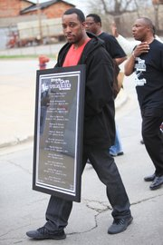 A participant in the Men of Valor 2's Stop the Gun Violence Epidemic prayer walk holds a sign listing the names of Joliet residents who have been killed by guns in the city.