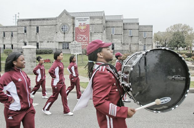 "marching band members entertain the audience. The commemoration began at the site of the former slave-holding pen known as Lumpkin's Jail in Shockoe Bottom, where VUU traces its origins. The American Baptist Home Mission Society began classes in 1865 to educate freed slaves. Gov. Terry McAuliffe, who spoke at the Shockoe Slip ceremony, urged the audience there to ""build upon what happened 150 years ago."""