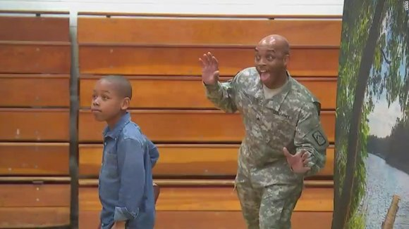 A soldier-dad returned home after a year to surprise his son at school during a photo shoot.