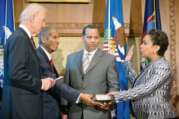 Loretta Lynch is sworn in Monday by Vice President Joe Biden, left, as the new U.S. attorney general in a ceremony at the Justice Department. Her father, Lorenzo Lynch, second from left, and husband, Stephen Hargrove, proudly hold the Bible.