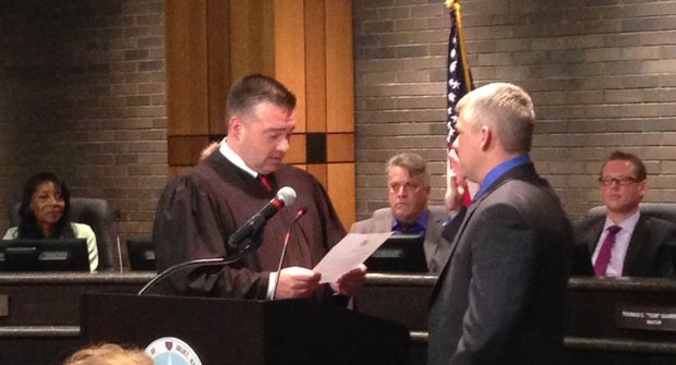 Joliet Mayor Bob O'Dekirk is sworn in to office Monday night by Will County Circuit Judge Mark Carlson, his former law partner. Council members Bettye Gavin (from left), Larry Hug and Jim McFarland watch from their council seats.