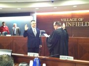 Brian Wojowski, a New Lenox police officer elected to his first term on the village board, takes the oath of office administered by Judge Dan Rippy, a Plainfield resident.