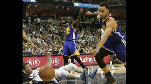 With Beno Udrih of the Grizzlies on the deck, Golden State's Stephen Curry eyes the loose ball, and Draymond Green helps the referee with the turnover call. Golden State evened the series 2-2, defeating Memphis 101-84.
