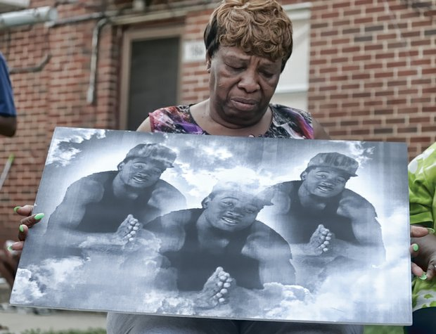 Joyce Kenney holds an image of her grandson, Ra'Keem Adkins, 22, who was shot and killed in the Mosby Court public housing community May 7.