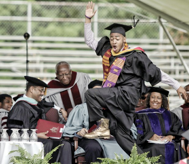 A happy Virginia Union University graduate and member of Omega Psi Phi Fraternity gives a celebratory stomp as he heads across the stage to collect his new degree.