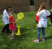 Troy Crossroads Elementary School preschool student Kendall Holverson swings a bat at the Young Athletes Culmination Event, with Lily McNeela (left), 3rd grade, and Josie Jarmuz (right), 4th grade, assisting.