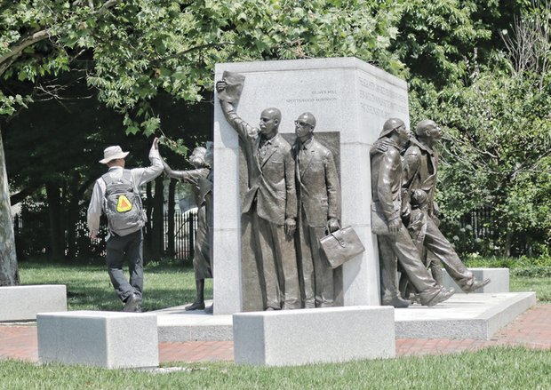 A passer-by gives a high-five to the likeness of Barbara Rose Johns at the Virginia Civil Rights Memorial at Capitol Square in Downtown. 