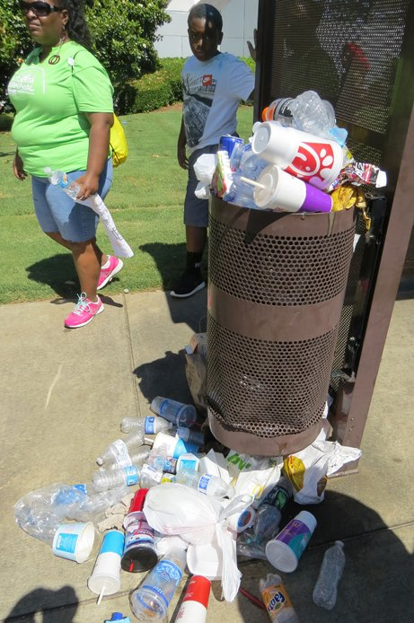 Trash overflows a  receptacle at a MARTA bus stop Saturday, one of the few places to put trash along the parade route.