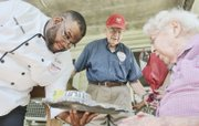 FeedMore Chef Amory M. James presents 102-year-old Helen Heinzen of the Lakeside community in Henrico County on Tuesday with the 7 millionth meal delivered by Meals on Wheels of Central Virginia as her son looks on.