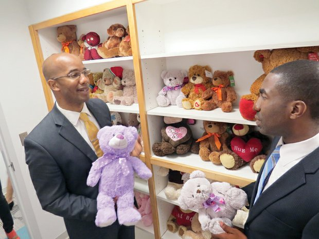 DeKalb District Attorney Robert James and interim CEO Lee May hold stuffed animals donated by businesses for child victims after a ribbon-cutting ceremony at the new DeKalb Family Protection Center in Tucker on May 28.