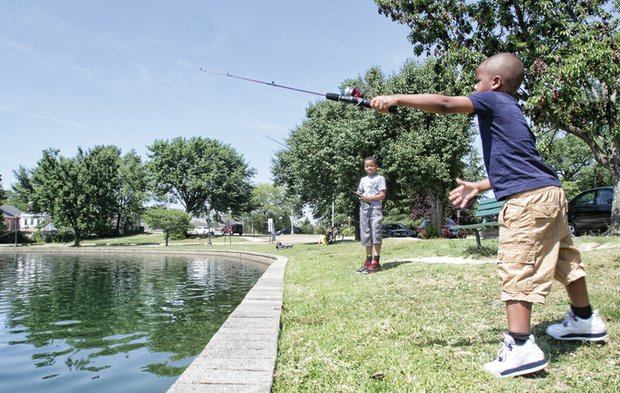 At Fountain Lake in Byrd Park, Kyjuan Ross, 9, looks on as his 5-year-old cousin, Nahjir King, casts his fishing line.