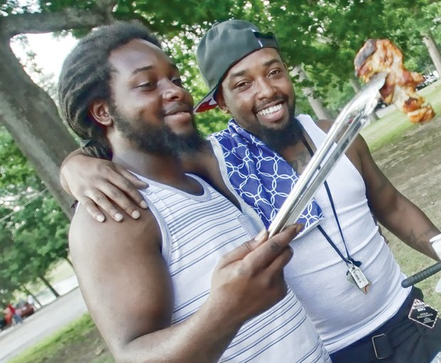 At Byrd Park, brothers Rashard and Winston Thornton check to see if the grilling chicken is done.