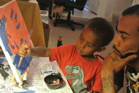 Twenty-eight-year old Artist Comacell Brown Jr. also known as Cell Spitfire, and Carmello Brown, age three, share a unique father-son ...