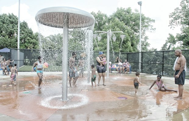 Parents and children enjoy the splash pad area at Battery Park Pool on North Side — one of the city's seven outdoor pools that opened during the weekend. The pools are popular places to cool off in the soaring summer heat. The pools are open seven days a week through Labor Day. The other six outdoor pools include Hotchkiss on North Side, Fairmount and Woodville in Church Hill, Powhatan in Fulton, Blackwell on South Side and Randolph in the near West End.