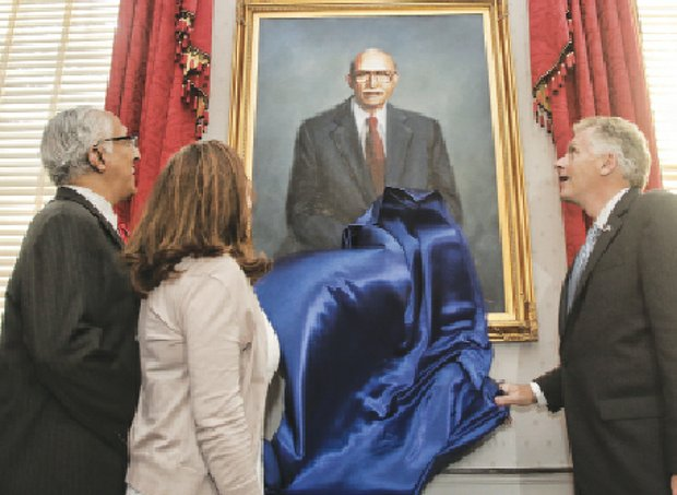 Gov. Terry McAuliffe, right, and his wife, Dorothy McAuliffe, are joined by Oliver W. Hill Jr., as they unveil a portrait of his father, legendary civil rights attorney Oliver W. Hill, at the Executive Mansion.