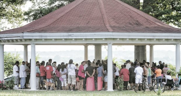 People gather Monday in Chimborazo Park in the East End to participate in a prayer vigil for the nine people who were murdered in Charleston, S.C.