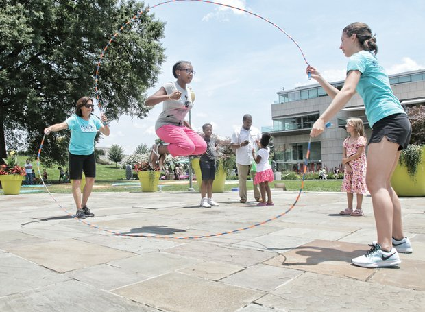 Indacia Turner, 11, shows off her skills in Double Dutch jump roping as Gail Kingrey and Abbie Dentler of the Swingers Jump Rope Team handle the ropes at the museum's Pauley Center Patio. Other activities included interactive games, creating Egungun-inspired masks and a musical performance by the Afrika Arkestra.