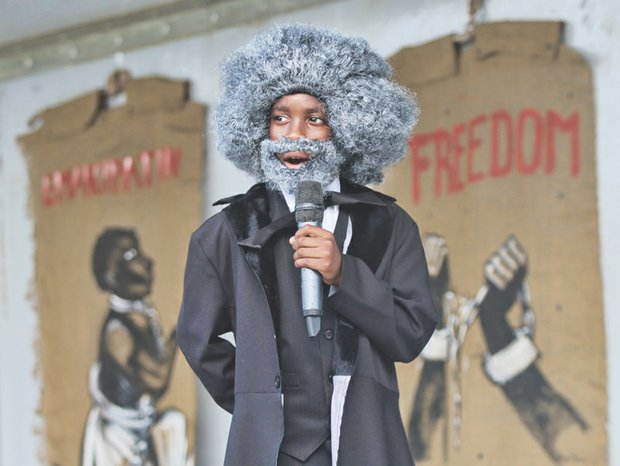 "JUNETEENTH- Scores of people gathered on South Side last Saturday to celebrate Juneteenth, the day that commemorates the announcement of the abolition of slavery in Texas on June 19, 1865. Right, Elijah Coles Brown, a gifted 11-year-old orator from Henrico County who donned a wig, beard and period dress, recites Frederick Douglass' famed ""The Meaning of July Fourth for the Negro"" speech. The speech attacked the hypocrisy of July 4th celebrations during times of enslavement."