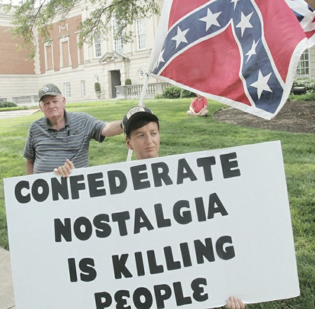 Sydney Lester of the Virginia Flaggers carries the Confederate battle flag during his group's protest last Saturday in front of the Virginia Museum of Fine Arts on the Boulevard. The museum has removed the symbol of hate from the Confederate Chapel located behind the museum. When the Virginia Flaggers were spotted, Camille Rudney and members of Justice 4 RVA arrived with their own signs in solidarity with Charleston, S.C., calling for the flag to be put away.