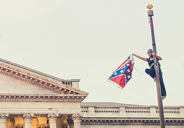 Bree Newsome boldly holds the Confederate flag after climbing the flagpole at the Statehouse in Columbia, S.C., to take it down last Saturday.