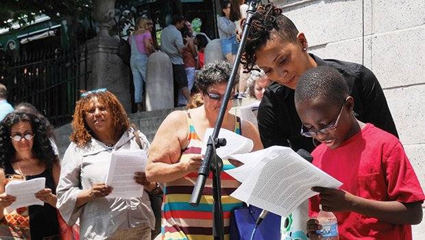 Karilyn Crockett, the City of Boston's director of economic policy and research, accompanied a young friend to the microphone during a public reading of Frederick Douglass's Fourth of July speech on July 1.