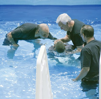 Wayne Rhodes, James Haney and James Rhodes perform a baptism ceremony.