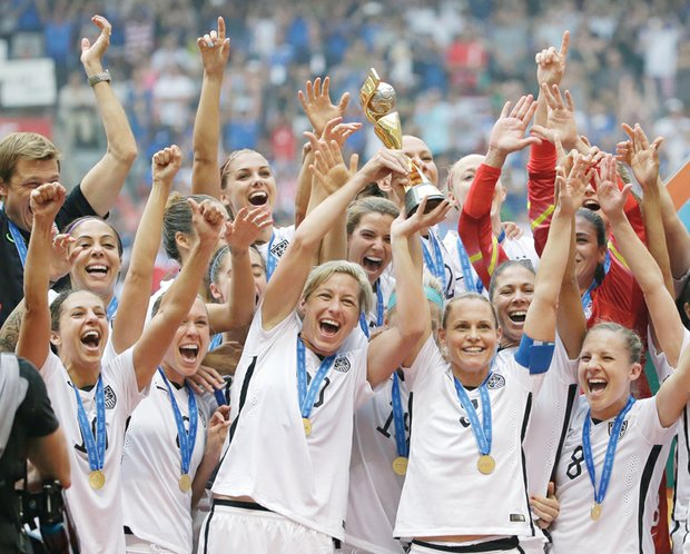 The U.S. Women's National Team celebrates with the trophy Sunday after they beat Japan 5-2 in the FIFA Women's World Cup soccer championship in Canada.